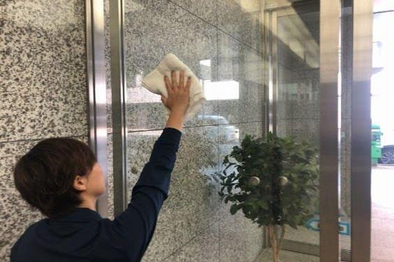 ファーストクリーン スタッフによりビル正面の入り口ガラスをきれいに身が空きあげている画像